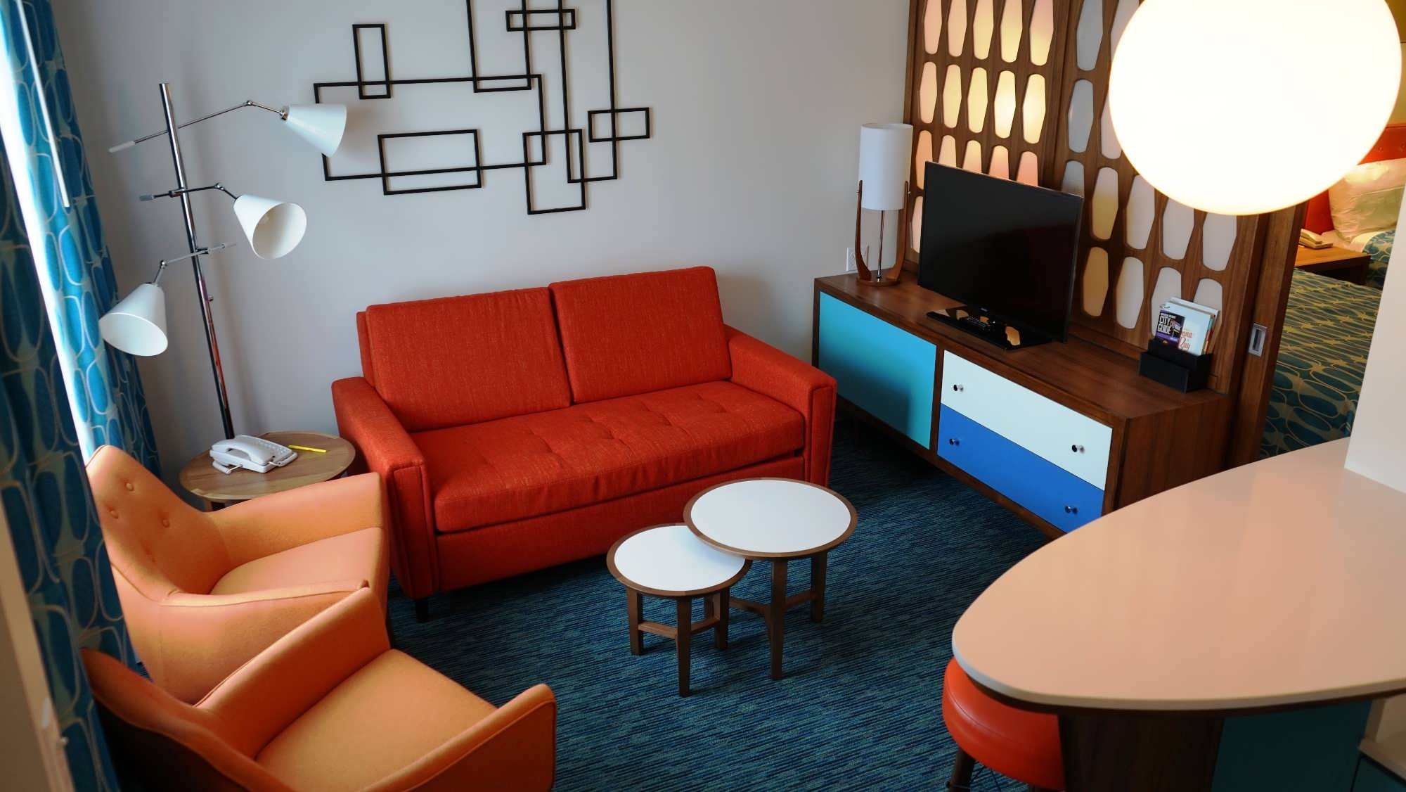 1950's style furniture with a modern flatscreen tv in the living space of a family suite at Cabana Bay