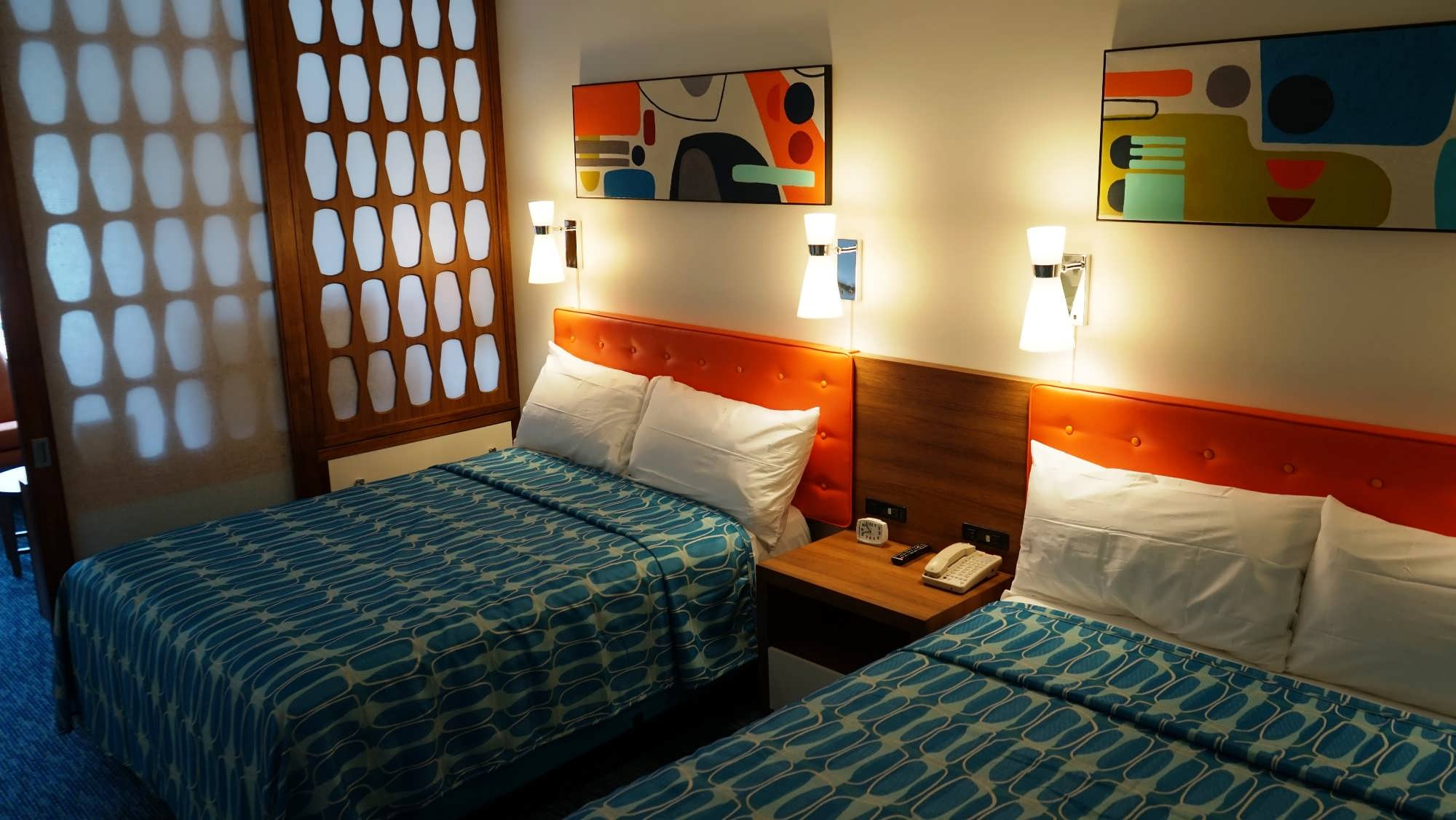 Two queen beds in the family suite at Cabana Bay Beach Resort, with retro-themed decor and partition