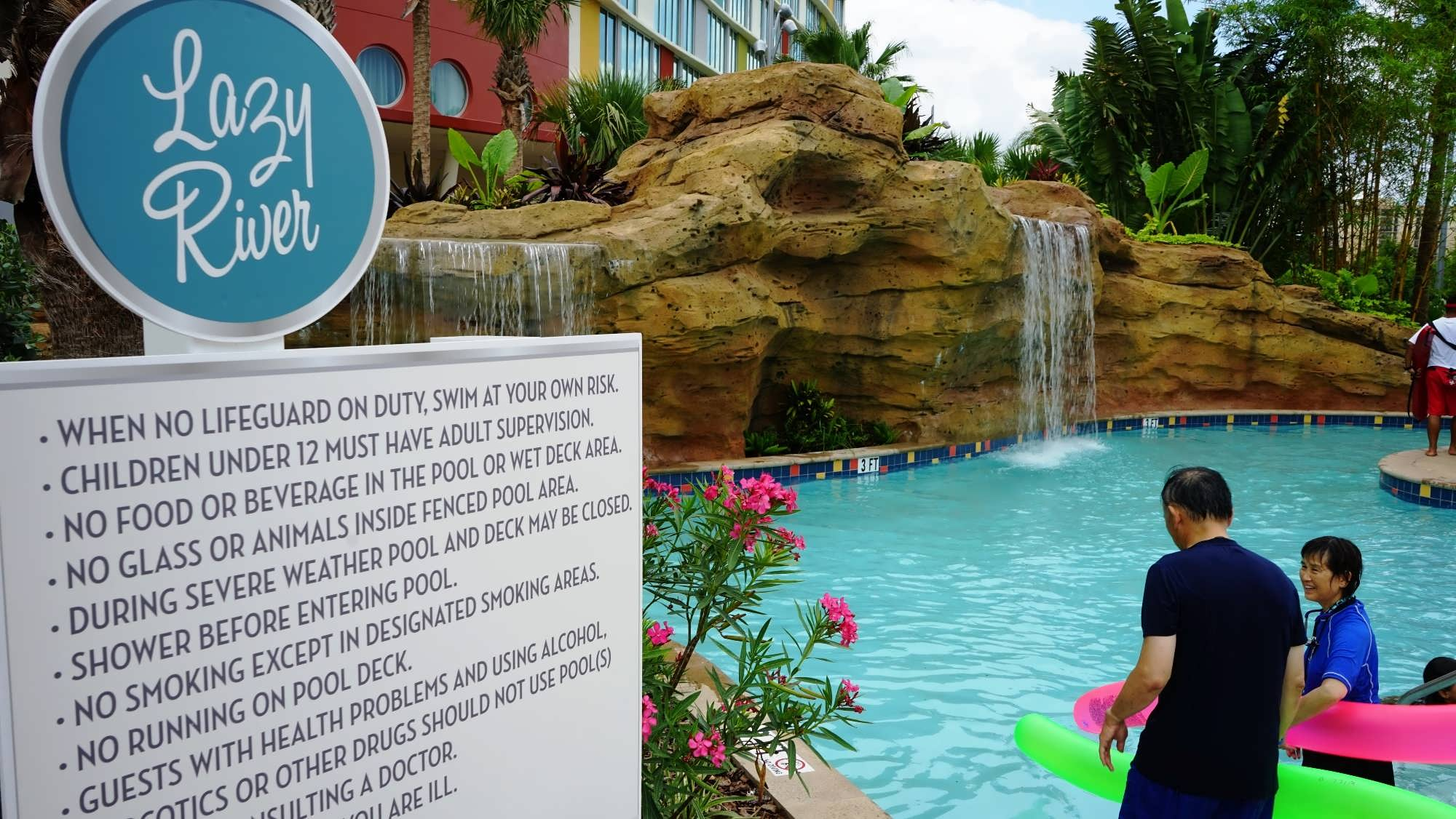 Guests enter the lazy river at Cabana Bay Beach Resort, as waterfalls spill down the rockwork into the river.