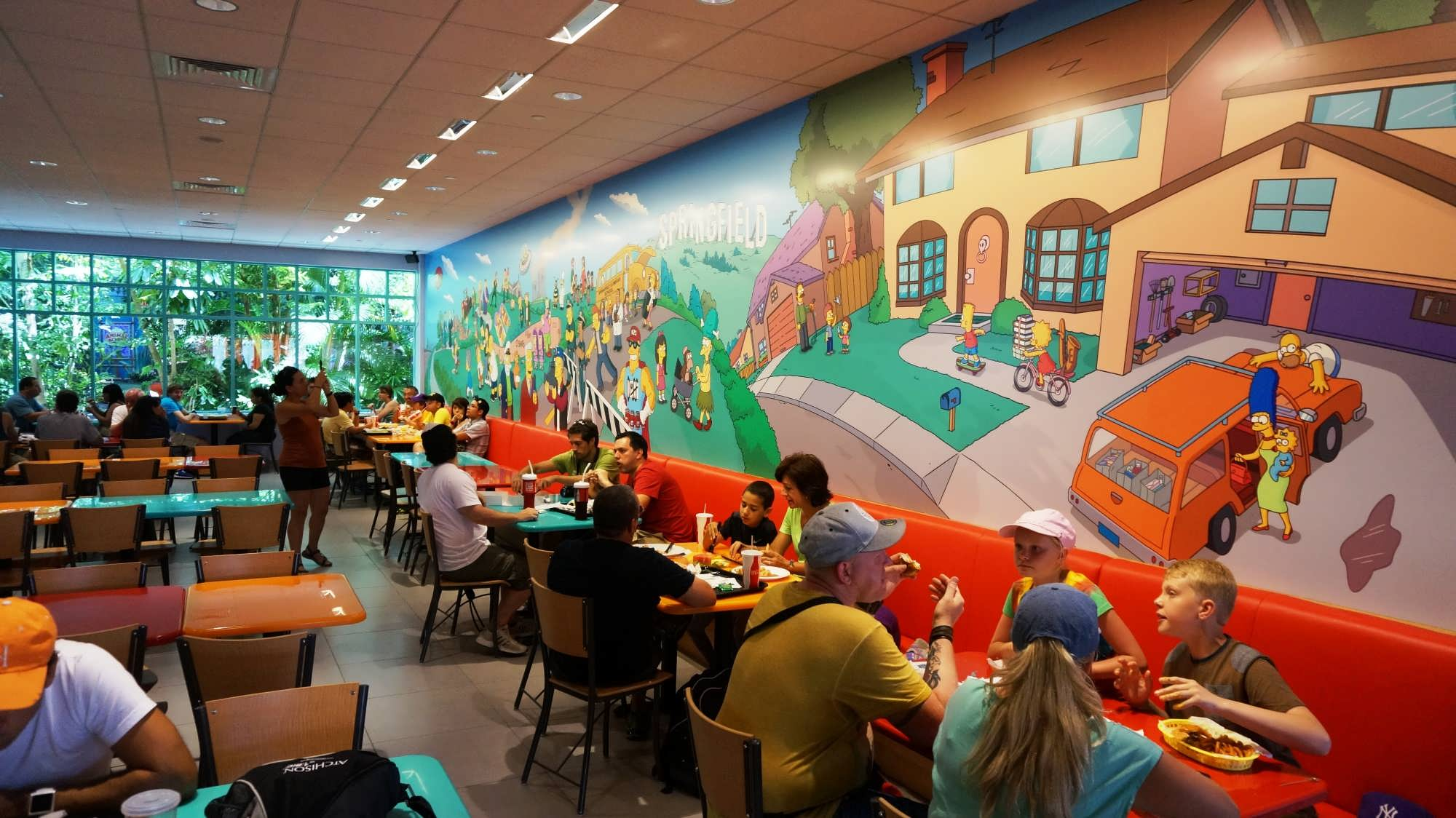 Diners eat at Fast Food Boulevard, with a wall mural featuring characters and locations from The Simpsons
