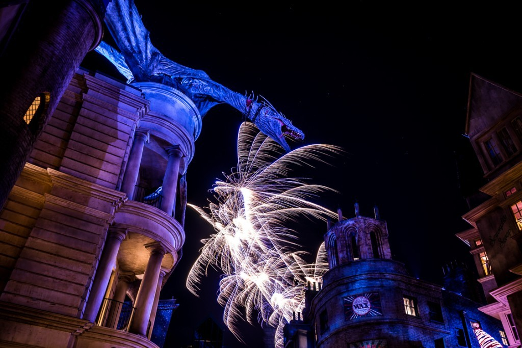 Diagon Alley with fireworks from Cinematic Spectacular in the background.