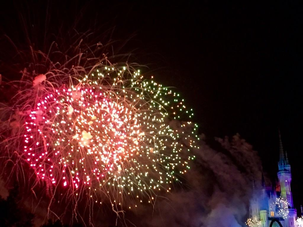 Red and gold fireworks exploding overhead to the left of Cinderall'as castle.