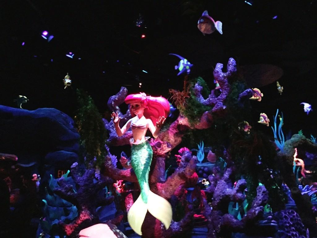 Ariel in the Little Mermaid Ride posing in front of a large colorful coral reef.