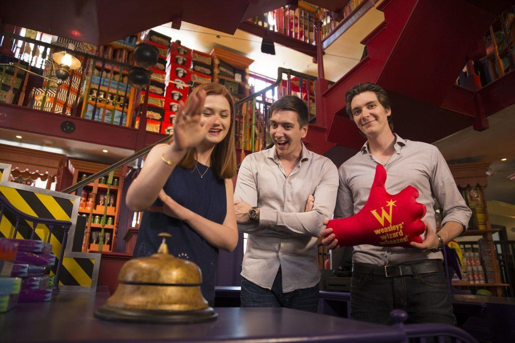 James and Oliver Phelps along with Bonnie Wright (Ginny) inside the Weasley's store. Ms. Wright is about to hit the bell that usually summons the pygmy puff naming
