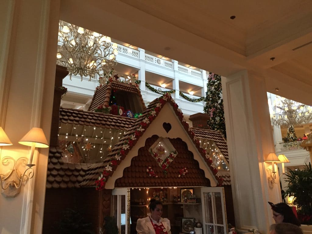 Giant gingerbread house in the Grand Floridian Hotel. Young woman is selling goodies inside.
