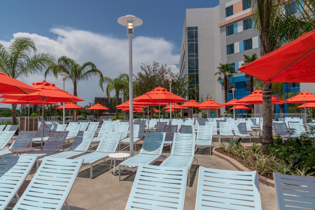 Rows of blue lounge chairs with red sun umbrellas at Surfside Inn and Suites