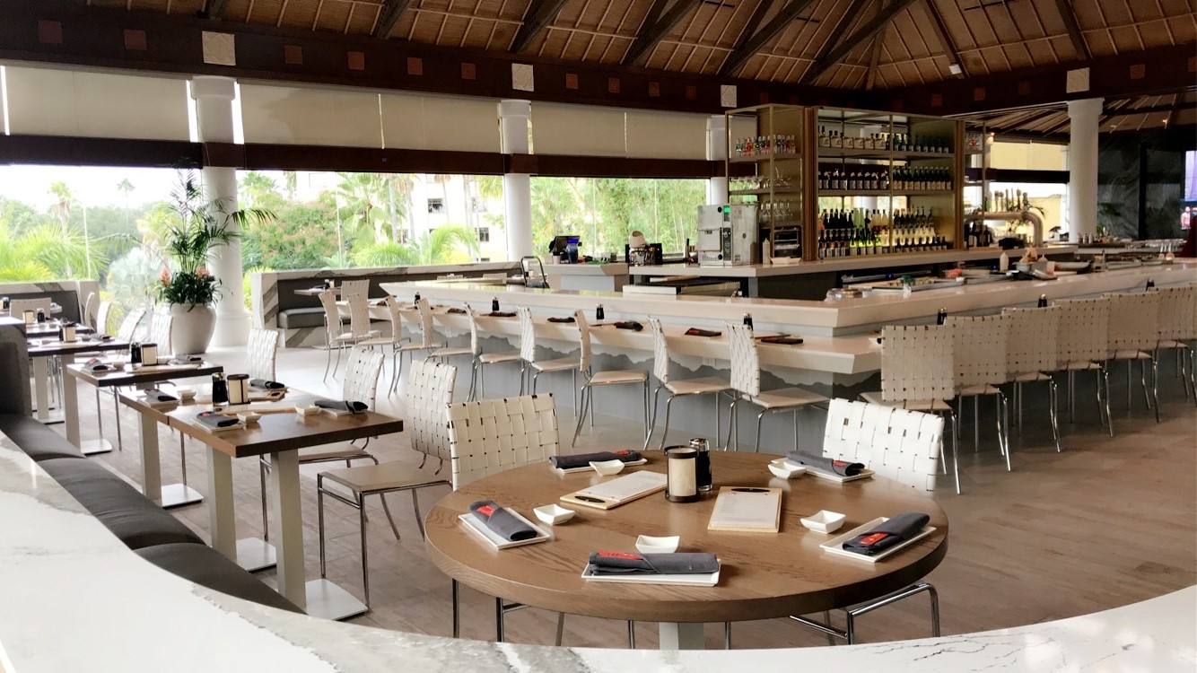 Tables surround the bar at Orchid Lounge, with a view out to the tropical landscaping at Royal Pacific Resort