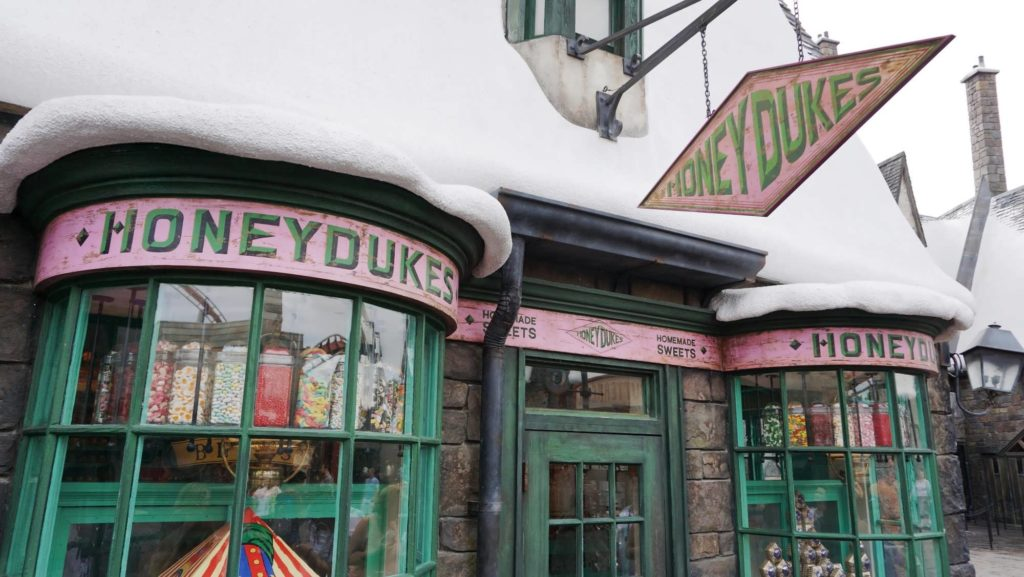The entrance to Honeydukes in Hogsmeade with window displays full of candies and treats