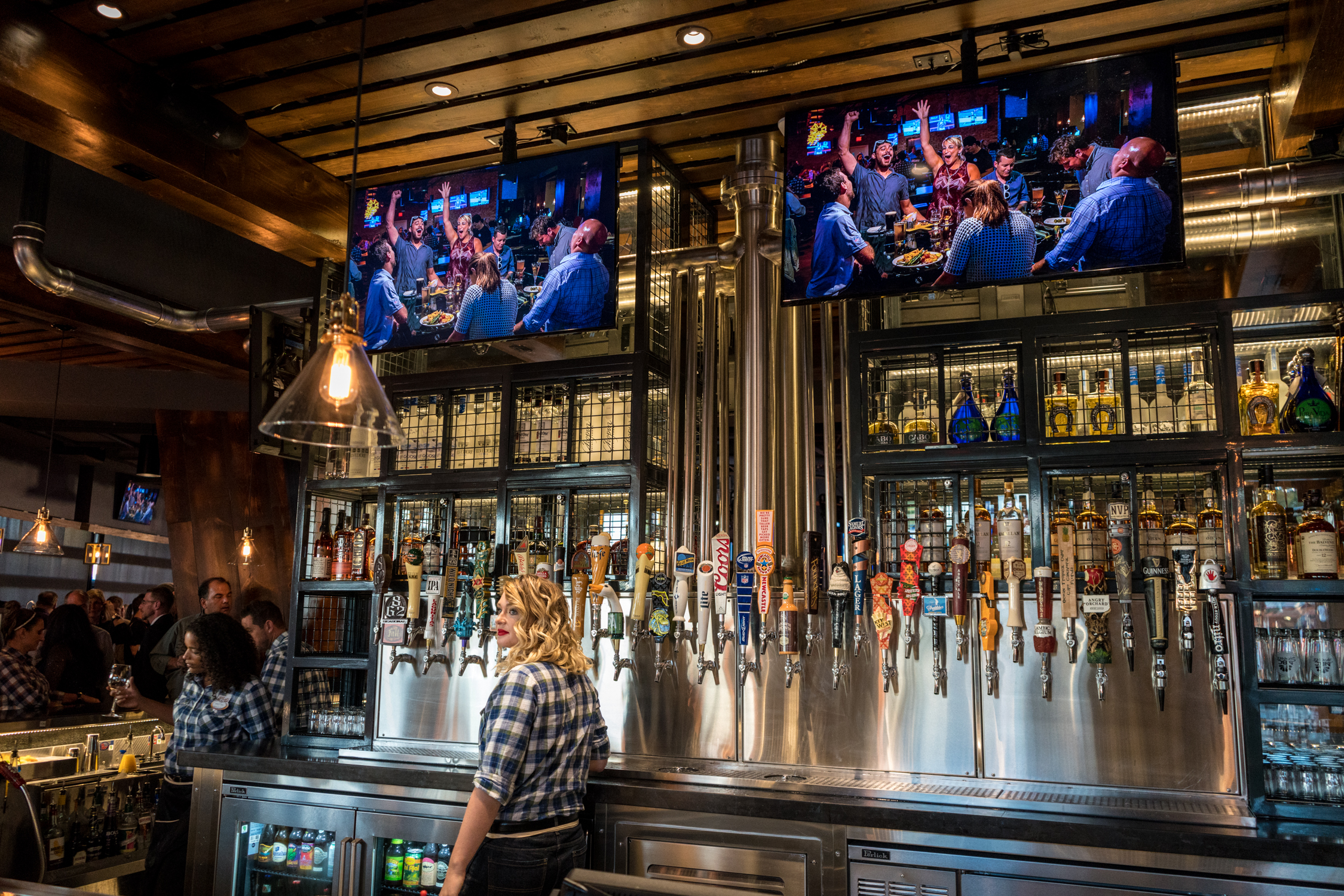 A large wall of draft beers on tap at NBC Sports Grill & Brew