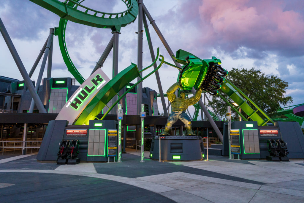 The entrance to the Incredible Hulk Coaster features a larger-than-life Hulk, lifting a roller coaster car above his head