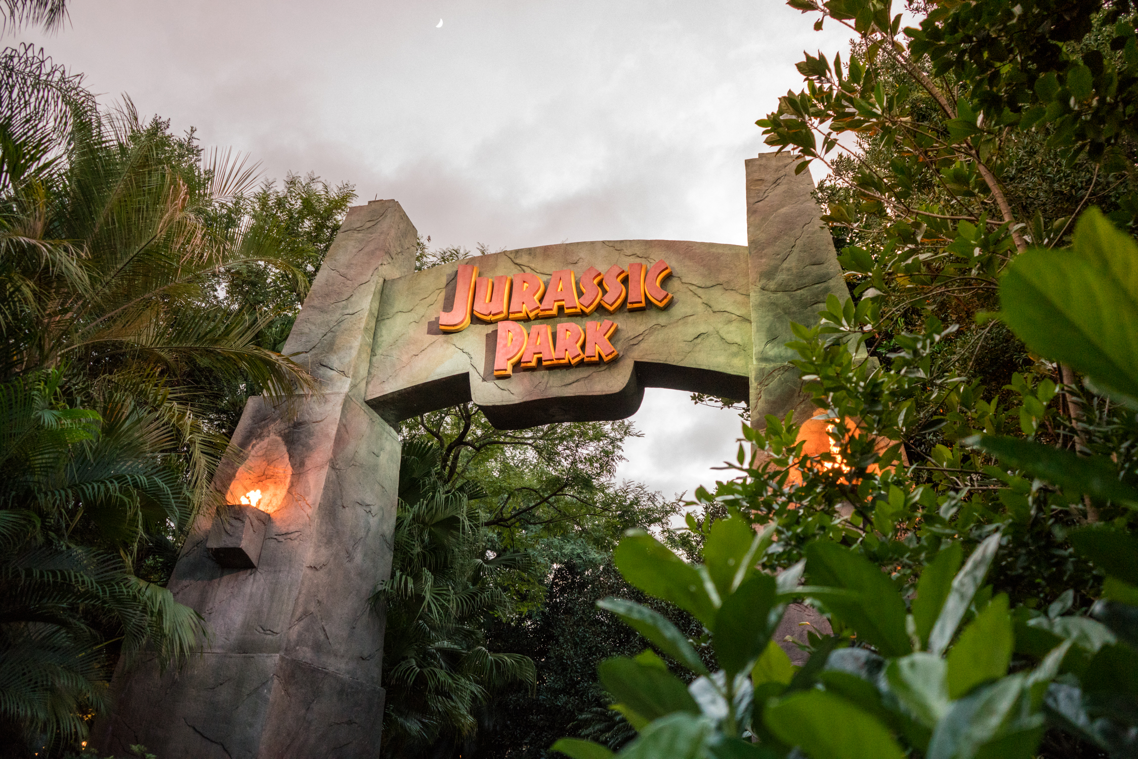 A stone gateway guards the entrance to Jurassic Park
