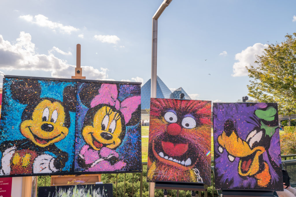 Disney-themed paintings for sale on display at EPCOT International Festival of the Arts