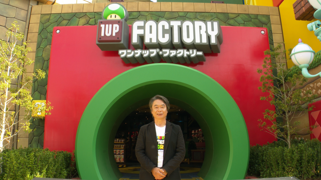 Shigeru Miyamoto at the entrance to the 1-Up Factory at Super Nintendo World