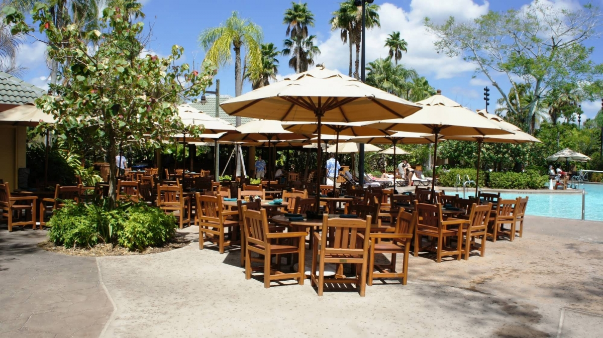 Tables are shaded by large umbrellas at the poolside Bula Bar & Grille