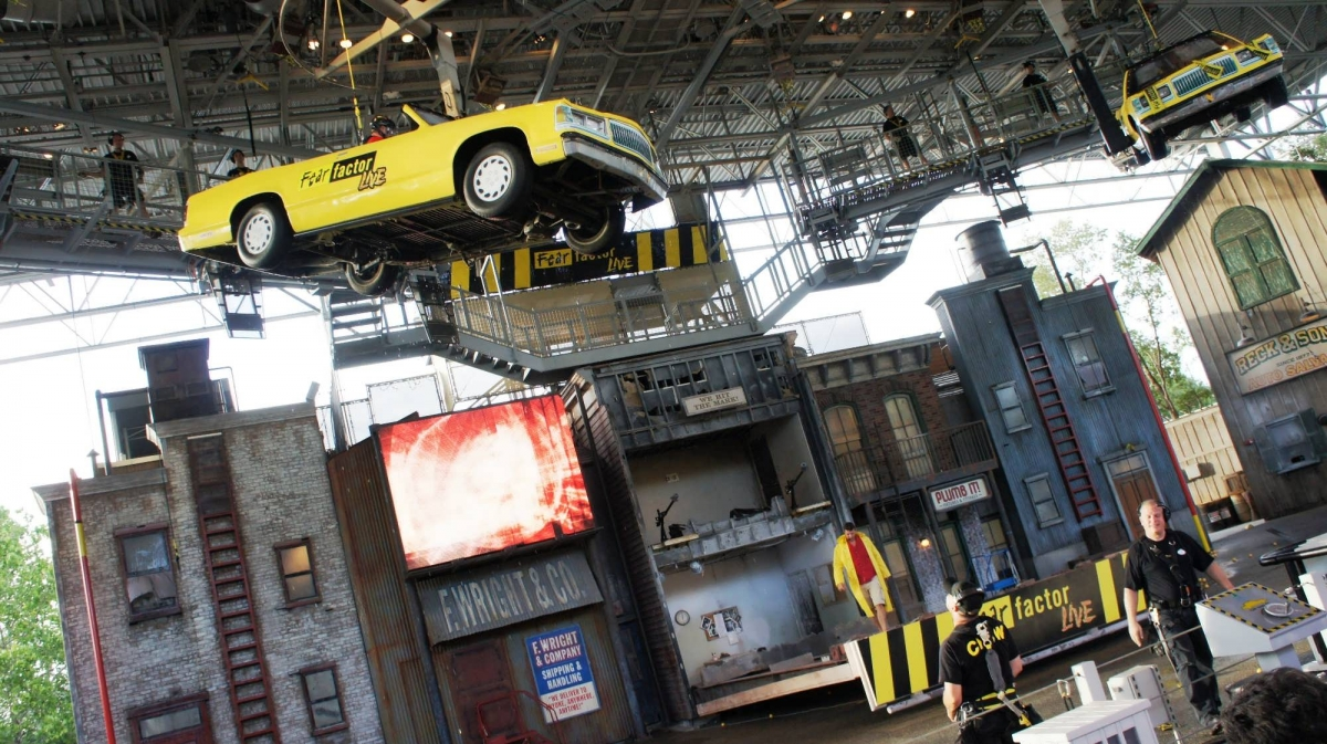 The stage of Fear Factor live has a city-block facade, and a stunt car hangs in the air while show techs look on