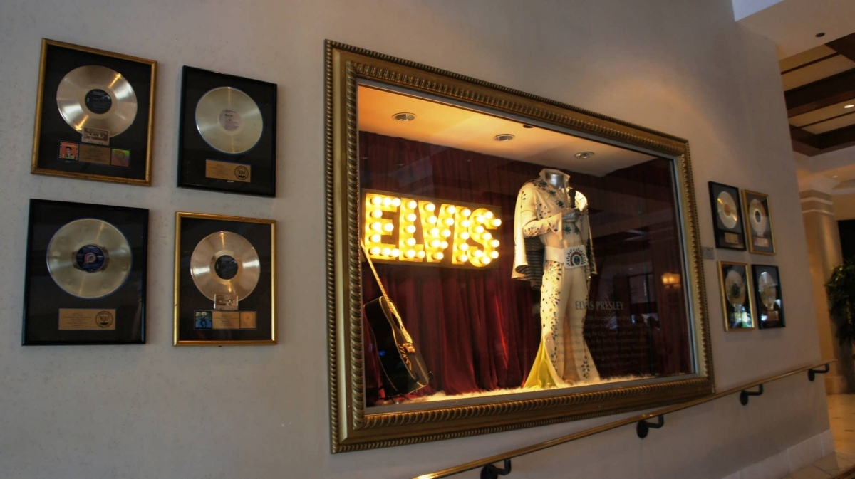 A window display features the famous white bellbottoms worn by Elvis Presley, and framed gold records are hung on the wall