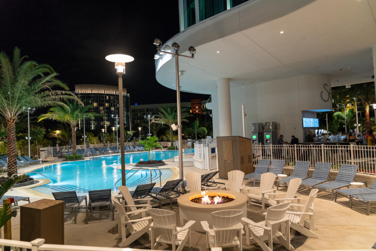 a fire pit lights up the Aventura Hotel pool at night