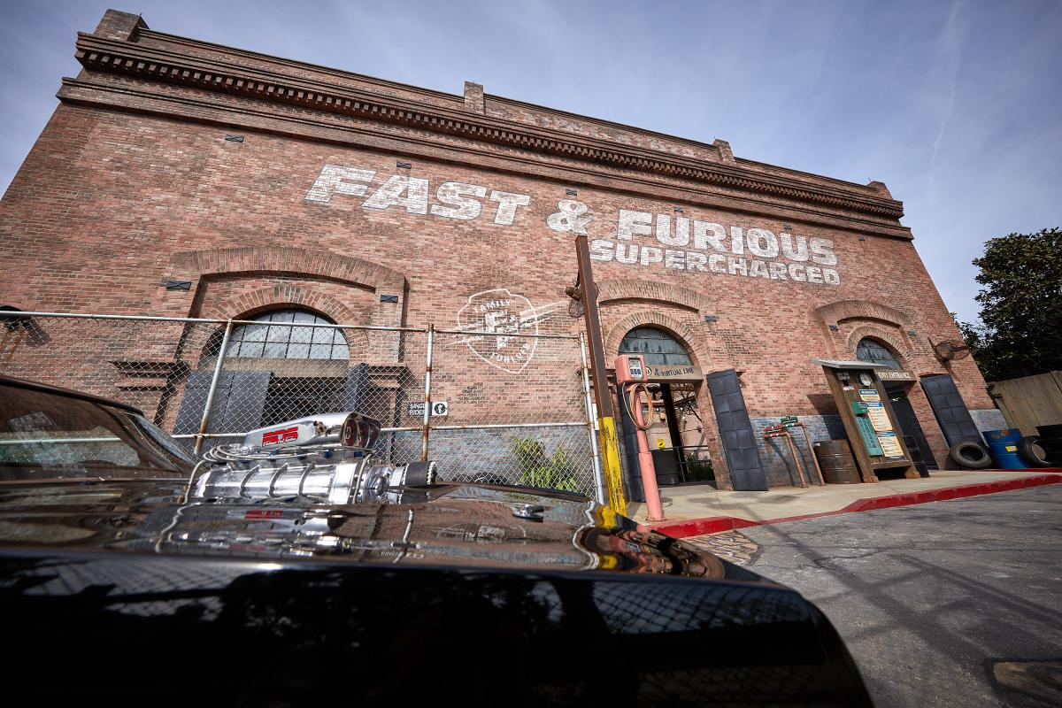 The facade of Fast & Furious - Supercharged garage warehouse with a black car in front