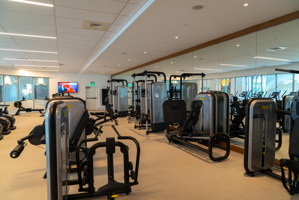 a variety of exercise machines at the Surfside Inn and Suites fitness center, with a mirrored wall and a television in the background