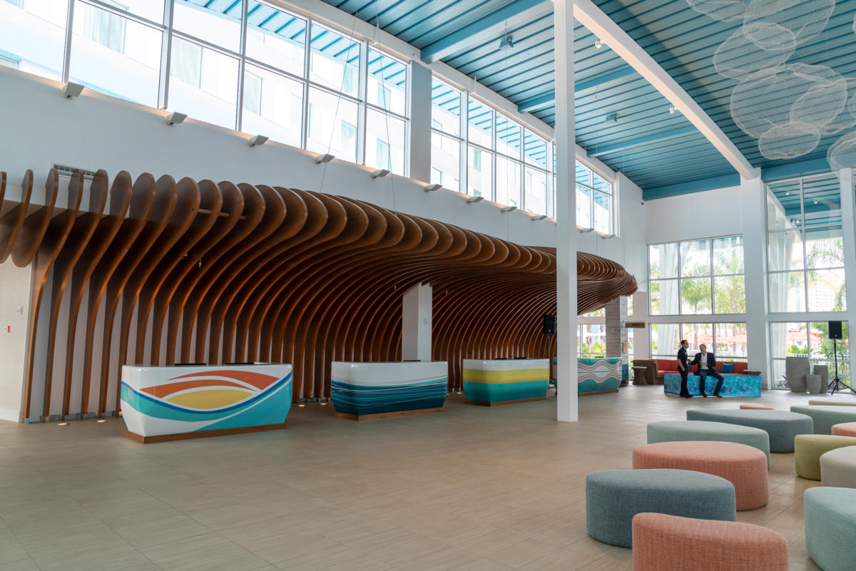 The check-in desk at the Surfside Inn and Suites lobby, with wooden wave sculpture and bubble-shaped light fixtures