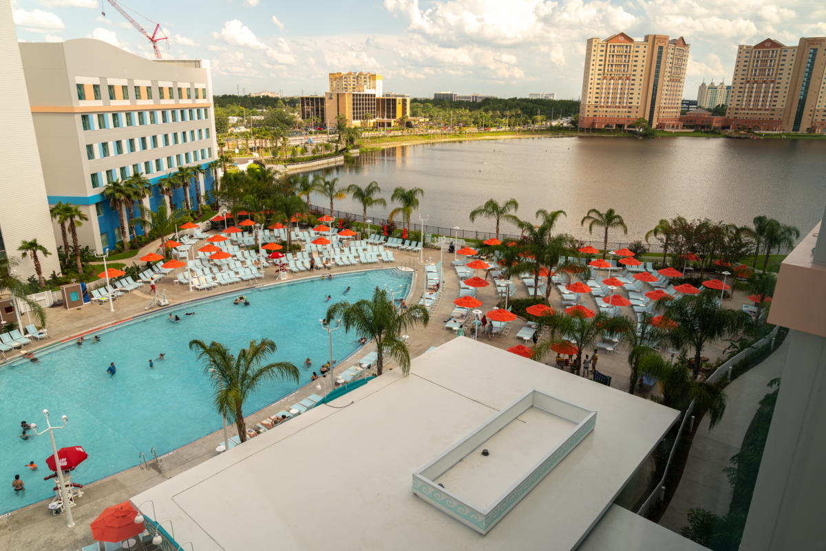 The surfboard-shaped pool at Surfside Inn and Suites is surrounded by beach lounge chairs and palm trees, and lies next to a lake.