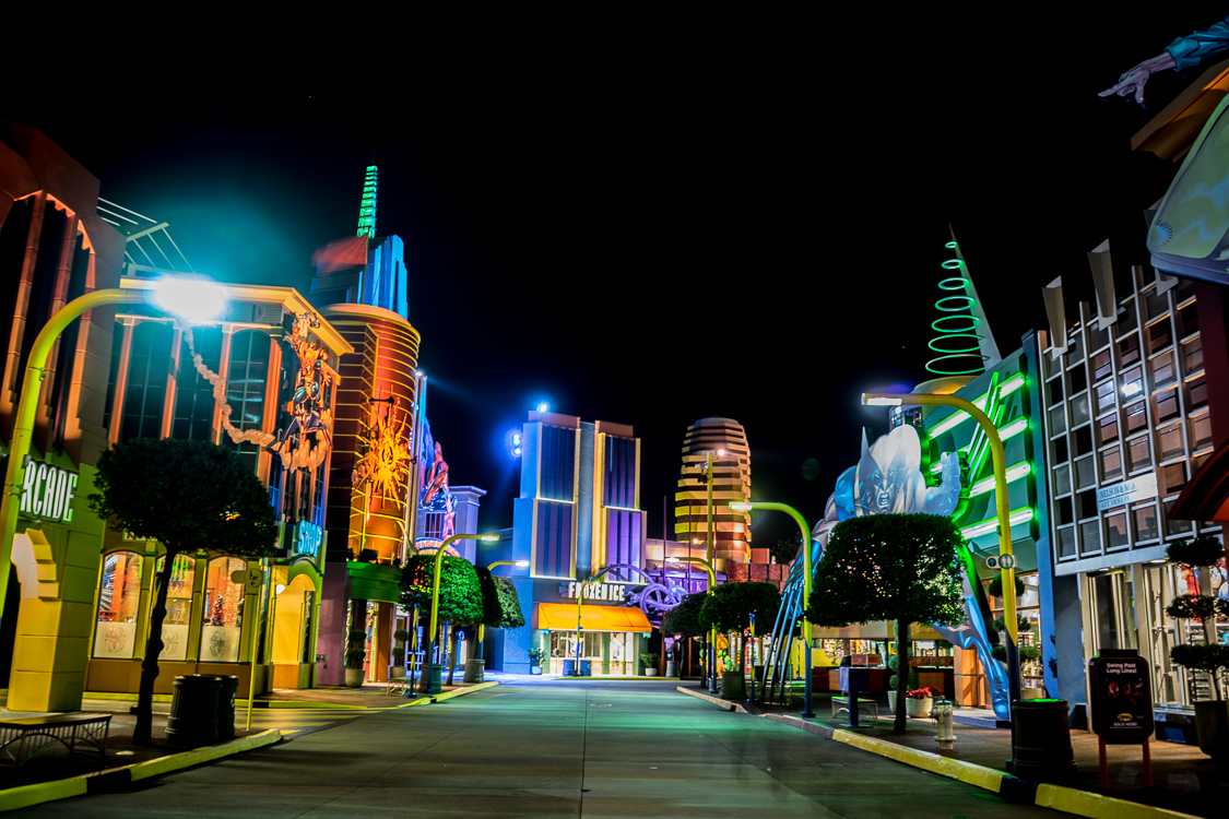 The buildings of Marvel Super Hero Island at night, with neon lighting
